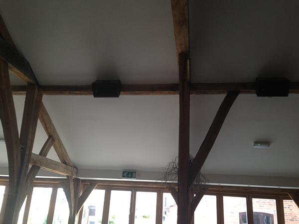 Black loudspeaker system installed into a hotel restaurant