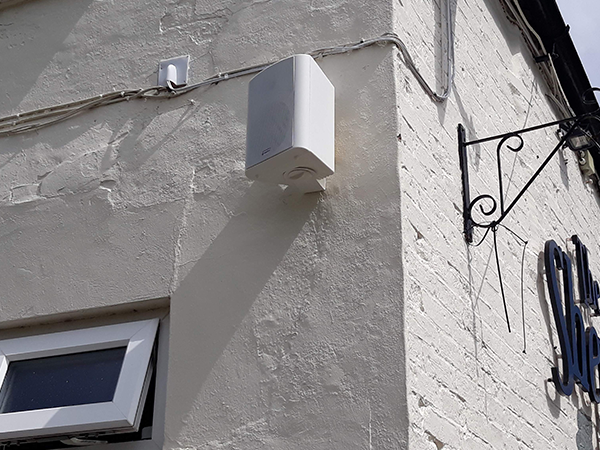 white outdoor speaker wallmounted on the building