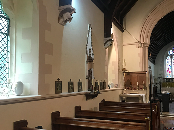white wall mounted pa speakers installed to the edge of the church for better sound distribution