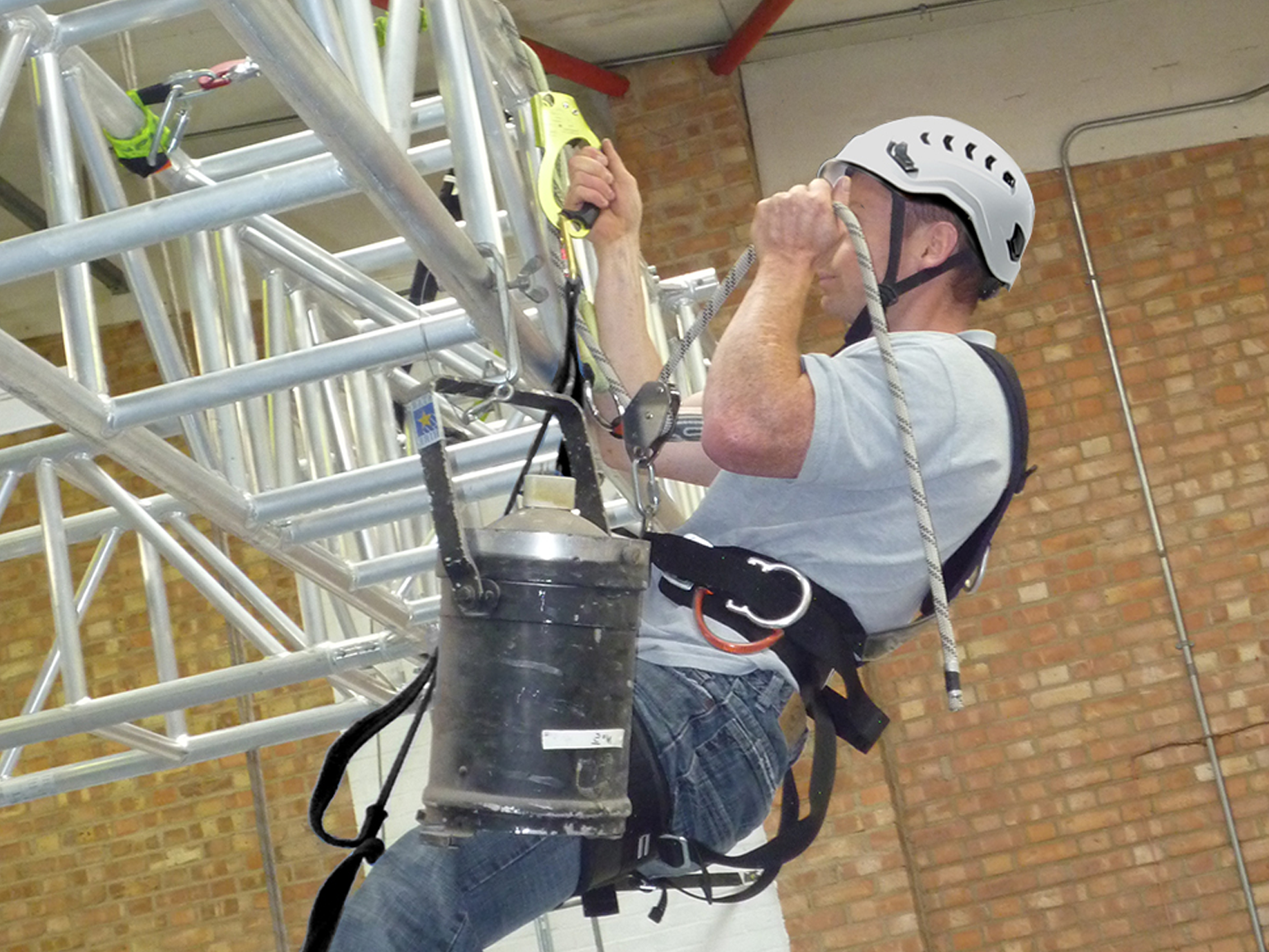 A man installing stage lighting into the ceiling of a theatre